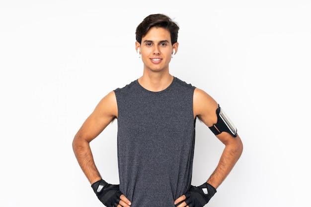 Homem de esporte isolado parede branca posando com os braços no quadril e sorrindo