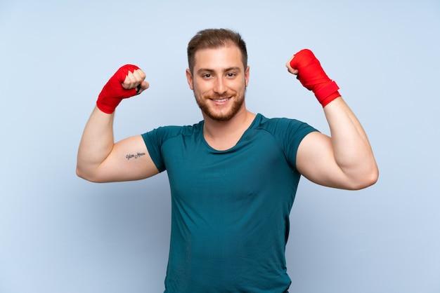Homem de esporte loiro sobre parede azul em ataduras de boxe