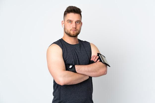Homem de esporte na parede branca com os braços cruzados