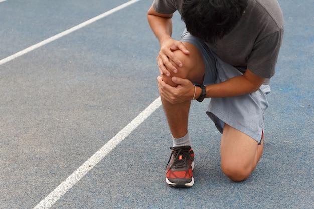 Homem de esporte que sofre com dor nos esportes, executando lesão no joelho após a execução. lesão do conceito de treino.