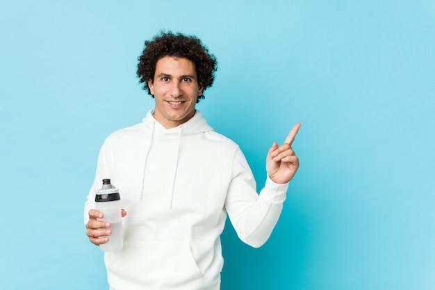 Homem de esporte segurando uma garrafa de água sorrindo alegremente apontando com o dedo indicador fora.
