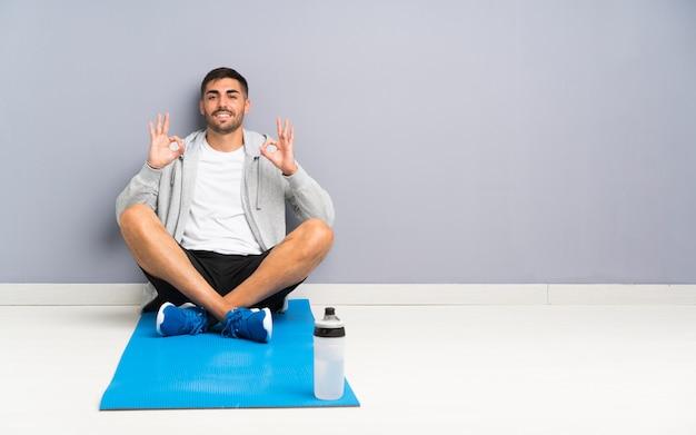 Homem de esporte sentado no chão, mostrando um sinal de ok com os dedos