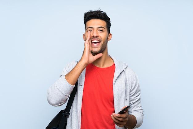 Homem de esporte sobre parede azul isolada, gritando com a boca aberta