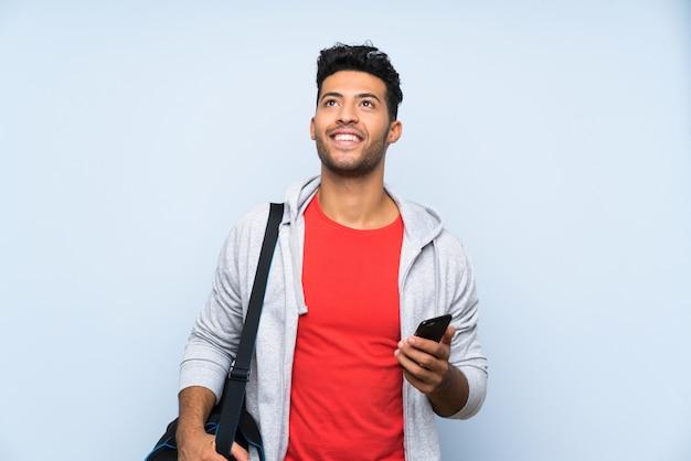 Homem de esporte sobre parede azul isolada, olhando para cima enquanto sorrindo