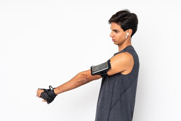 Homem de esporte sobre parede branca, esticando o braço