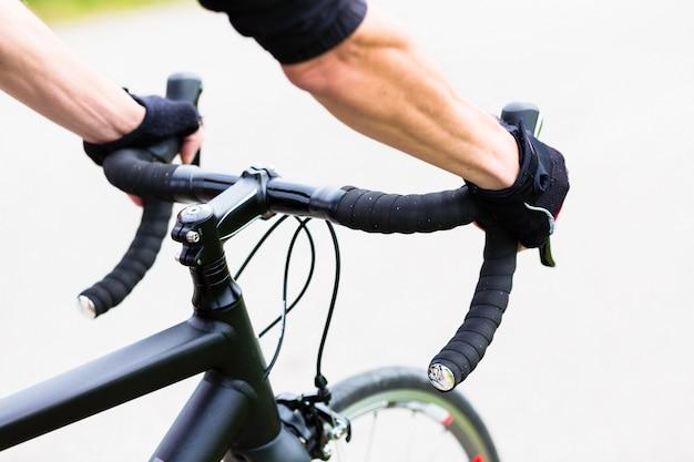 Homem de esporte, tendo as mãos no guidão de bicicleta de corrida