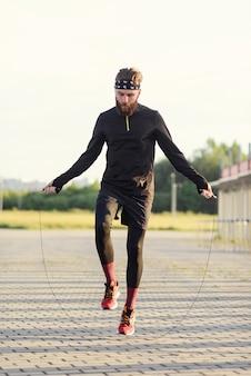 Homem de esportes fitness pulando com corda de pular ao ar livre