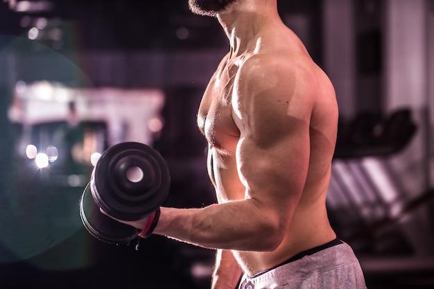 Homem de esportes musculares está envolvido no treinamento de cross fit na academia, o conceito de esporte