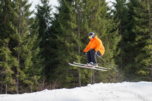 Homem de esquiador voador no salto da encosta das montanhas