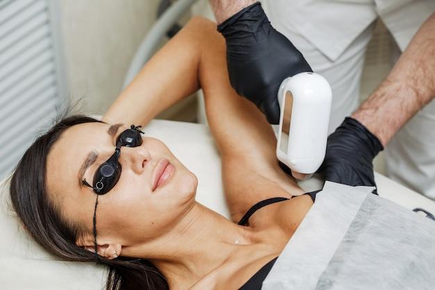 Homem de esteticista, aplicação de depilação a laser ou depilação a laser na zona das axilas para mulher no salão spa