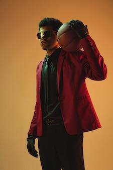 Homem de estilo de alta costura com jaqueta vermelha jogando basquete isolado sobre a parede marrom. excelente desportista profissional afro-americano, desempenho de atleta, treinamento. juventude, liberdade, anúncio, vendas.