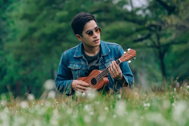 Homem de estilo de vida relaxante no parque com seu tom vintage ukulele