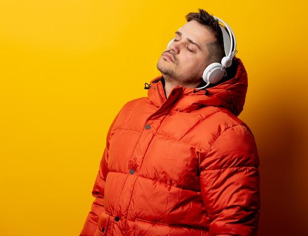 Homem de estilo na jaqueta dos anos 90 com fones de ouvido na parede amarela
