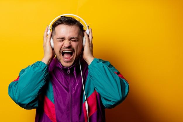 Homem de estilo no agasalho dos anos 90 com fones de ouvido na parede amarela