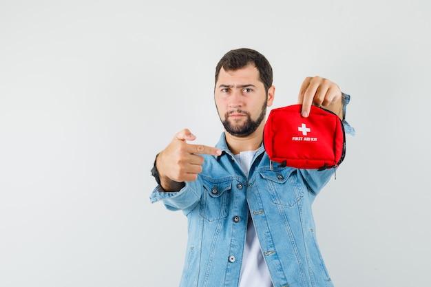 Homem de estilo retro com jaqueta, camiseta, apontando para o kit de primeiros socorros e olhando sério, vista frontal. espaço para texto