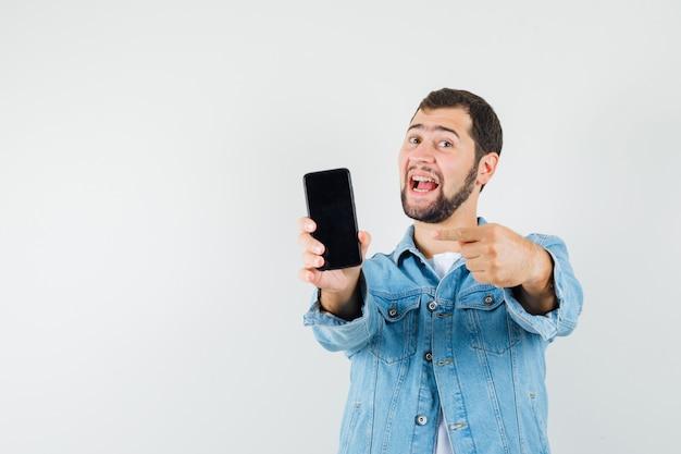 Homem de estilo retro com jaqueta, camiseta, apontando para o telefone celular e olhando positiva, vista frontal.