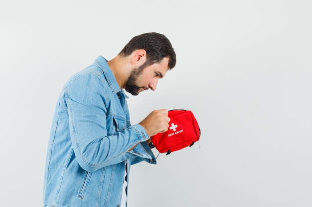 Homem de estilo retro com jaqueta, camiseta olhando para o kit de primeiros socorros e parecendo concentrado.