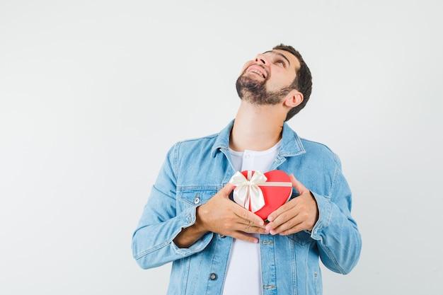 Homem de estilo retrô mostrando caixa de presente em forma de coração na jaqueta, camiseta e olhando ansioso, vista frontal.