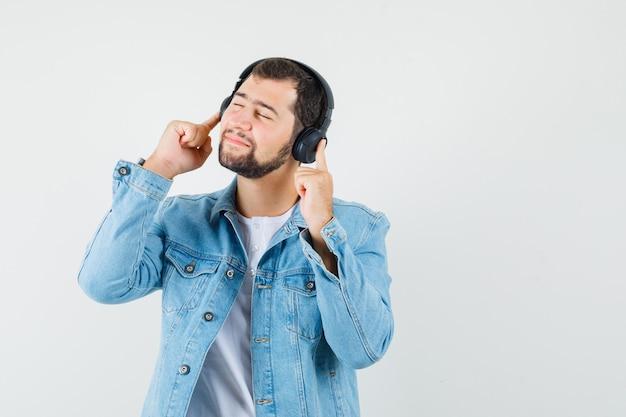 Homem de estilo retro ouvindo música com fones de ouvido na jaqueta, camiseta e parecendo relaxado, vista frontal.