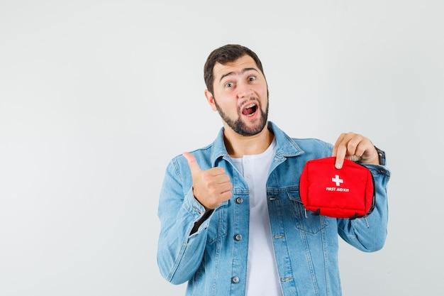 Homem de estilo retro segurando o kit de primeiros socorros enquanto aparece o polegar na jaqueta, camiseta e parece otimista. vista frontal.