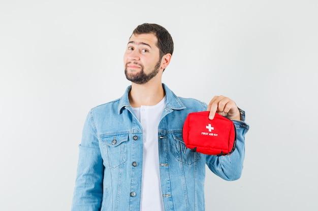 Homem de estilo retro segurando o kit de primeiros socorros na jaqueta, camiseta e olhando otimista, vista frontal.