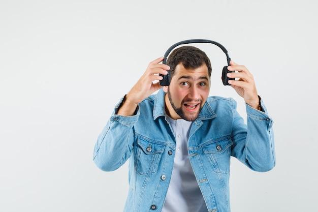 Homem de estilo retro usando fones de ouvido na jaqueta, camiseta e parecendo enérgico, vista frontal.