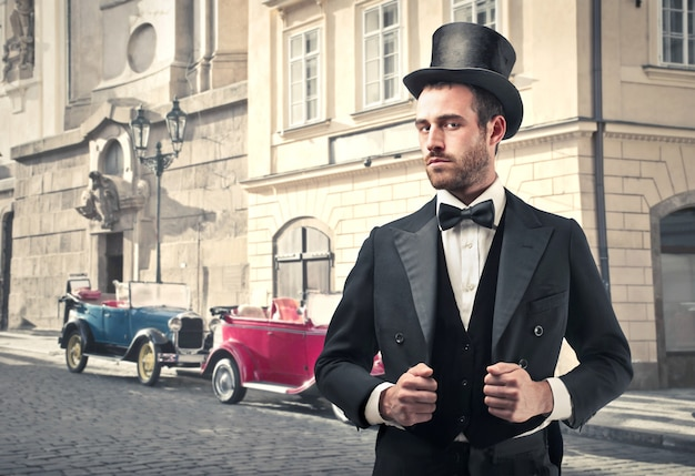 Homem de estilo vintage com carros antigos no fundo