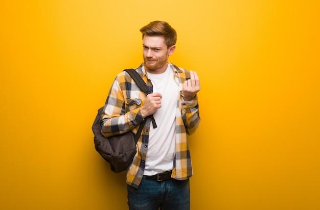 Homem de estudante jovem ruiva fazendo um gesto de necessidade