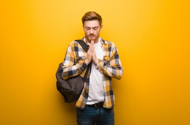 Homem de estudante jovem ruiva rezando muito feliz e confiante