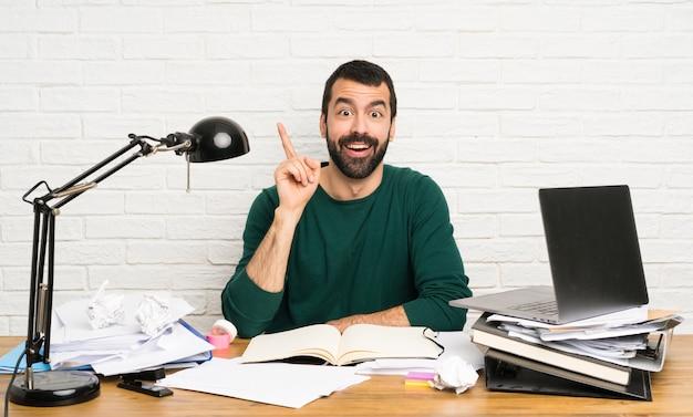 Homem de estudante pensando uma ideia apontando o dedo para cima
