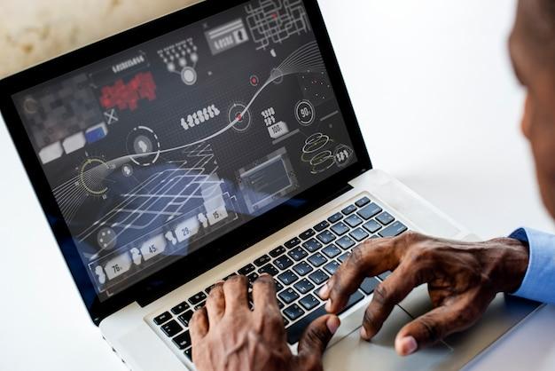 Homem de etnia africana, trabalhando com infográfico no laptop