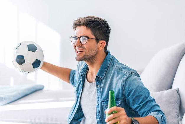 Homem de fã de futebol fanático assistindo jogo de futebol na tv comemorando