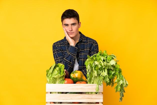 Homem de fazendeiro adolescente com legumes recém colhidos em uma caixa infeliz e frustrada