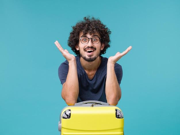 Homem de férias com uma grande mala amarela se sentindo feliz no azul