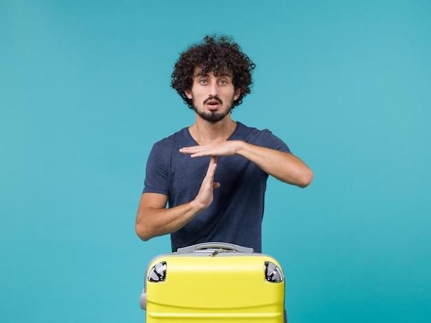 Homem de férias mostrando sinal t azul