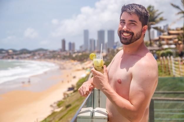 Homem de férias no resort tomando um drinque com a praia ao fundo