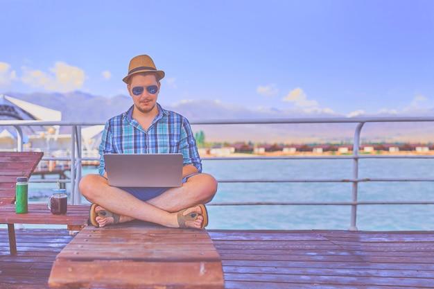Homem de férias, senta-se na espreguiçadeira no cais e trabalha com smoothie.