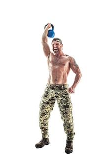 Homem de fisiculturista atleta muscular em calças de camuflagem com um torso nu fazendo fitness kettlebells balanço exercício em branco