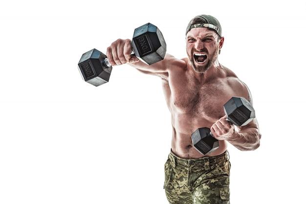 Homem de fisiculturista atleta muscular em calças de camuflagem com um torso nu, socando com halteres como boxeador