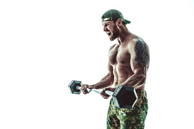 Homem de fisiculturista atleta muscular em calças de camuflagem com um treino de tronco nu com halteres em branco