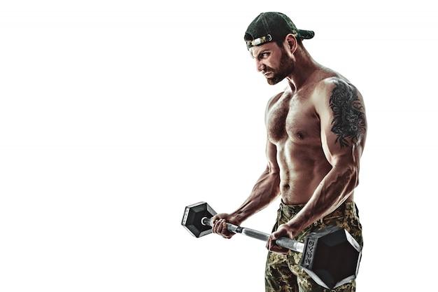 Homem de fisiculturista atleta muscular em calças de camuflagem com um treino de tronco nu com halteres em uma parede branca.