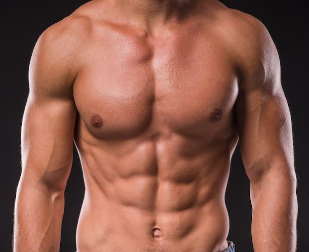 Homem de fisiculturista com corpo perfeito, ombros, bíceps.