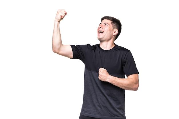 Homem de fitness animado com gesto de vencedor na parede branca