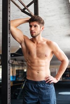 Homem de fitness de moda no ginásio. desviando o olhar