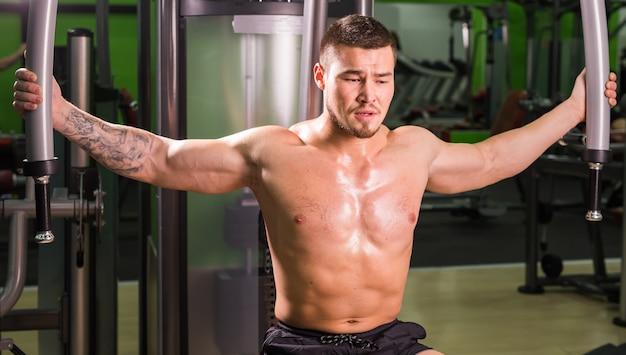 Homem de fitness de raça mista está trabalhando na máquina de borboletas no ginásio.