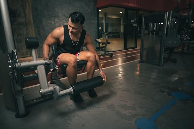 Homem de fitness espacial com máquina de treinamento de pernas na academia