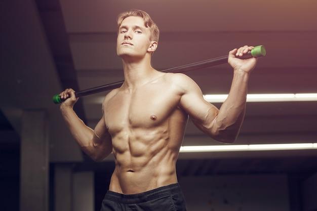 Homem de fitness fazendo exercícios na academia com barra corporal alongando os músculos