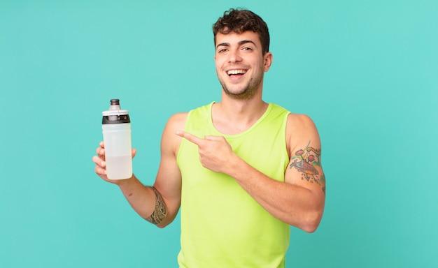 Homem de fitness parecendo animado e surpreso, apontando para o lado e para cima para copiar o espaço
