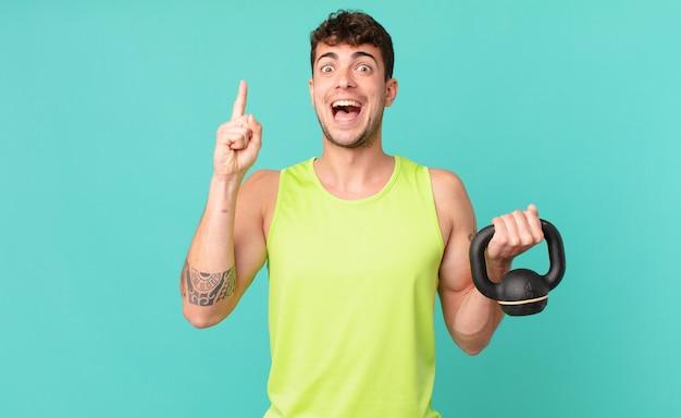Homem de fitness se sentindo um gênio feliz e animado depois de realizar uma ideia, levantando o dedo alegremente, eureka!