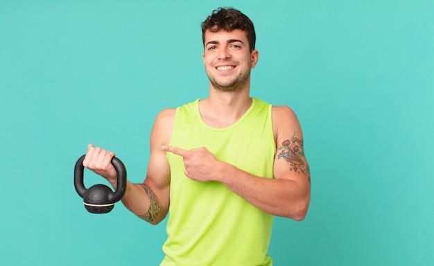 Homem de fitness sorrindo alegremente, sentindo-se feliz e apontando para o lado e para cima, mostrando o objeto no espaço da cópia